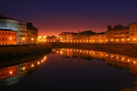Pisa by night reflecting in the Arno river
